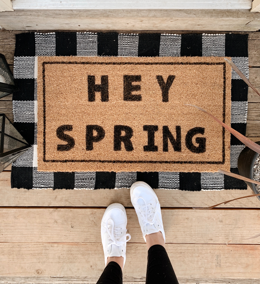 """feet standing next to a welcome mat that reads """"hey spring"""""""
