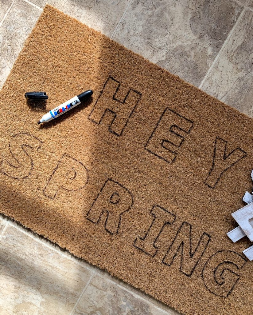 """the phrase """"hey spring"""" traced on a mat"""