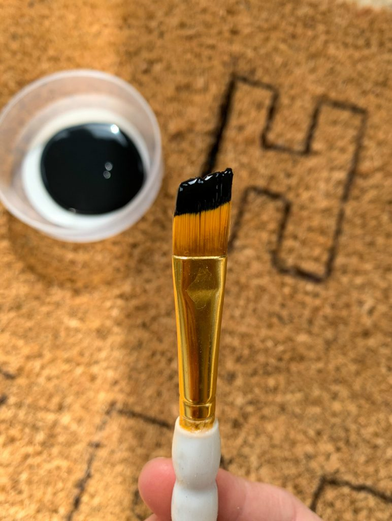 small paint brush dipped in black paint