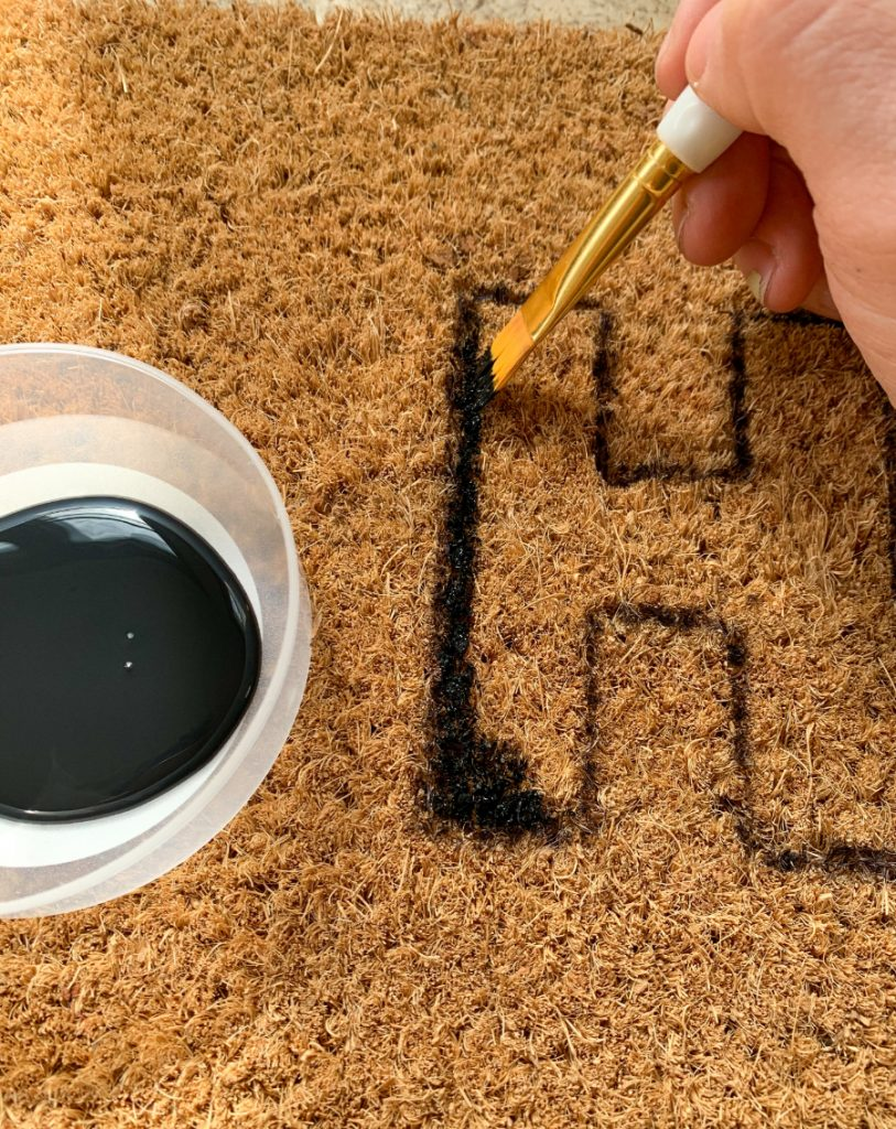 hand holding a paint brush dipped in black paint outlining the letter H on the welcome mat