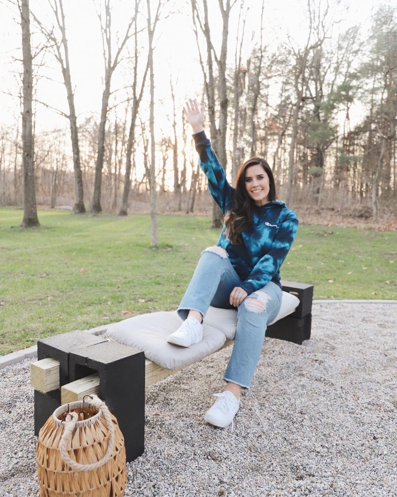 girl sitting on a bench with her hand raised in the air