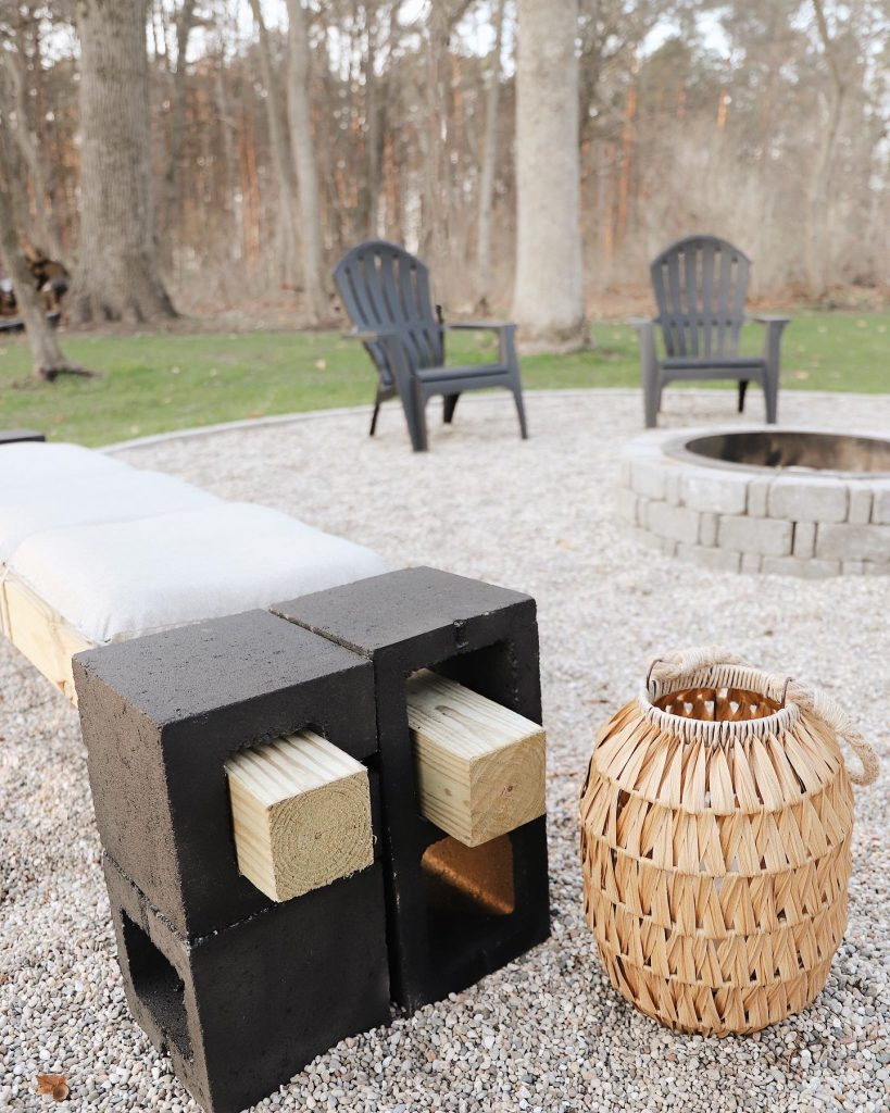 simple outdoor bench made from cinder blocks on a patio next to a fire pit