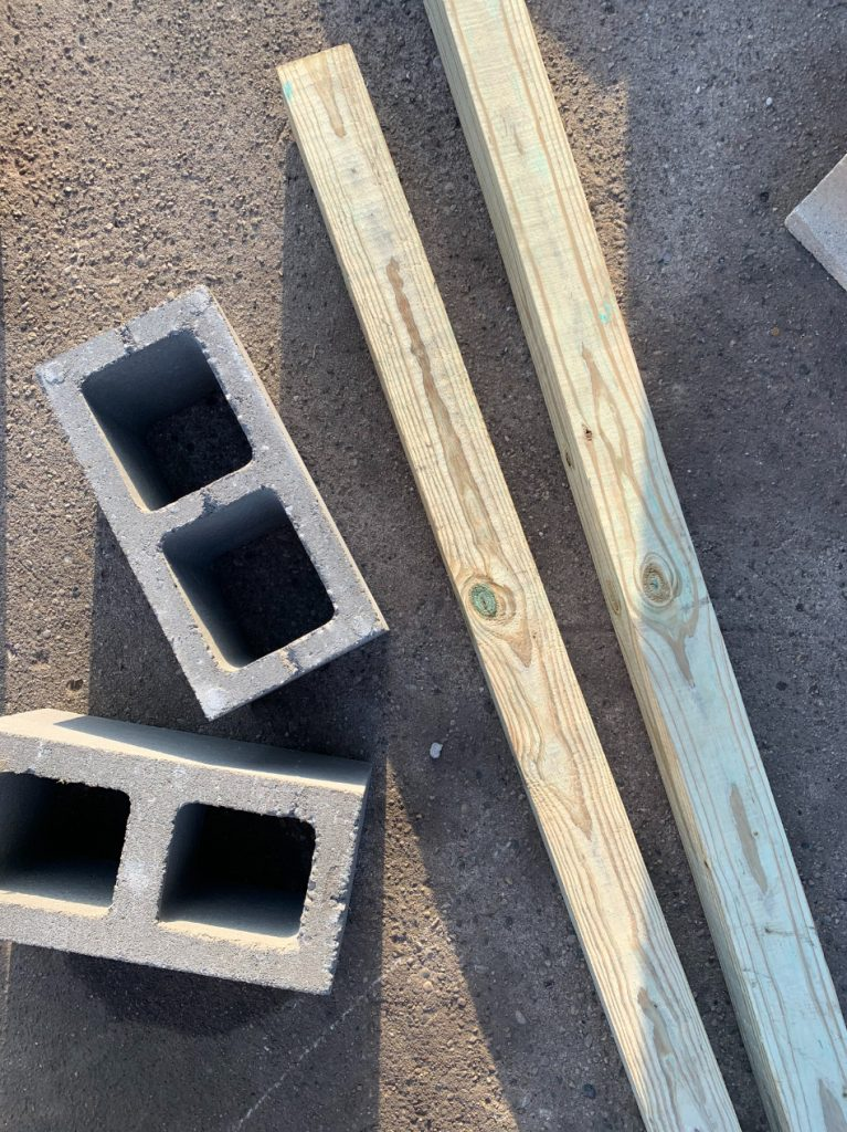 two grey cinder blocks laying next to two 4x4 wood posts