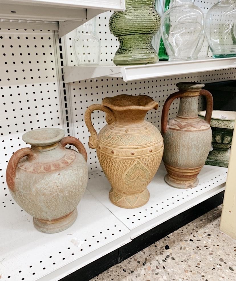 three clay pottery on a white shelf