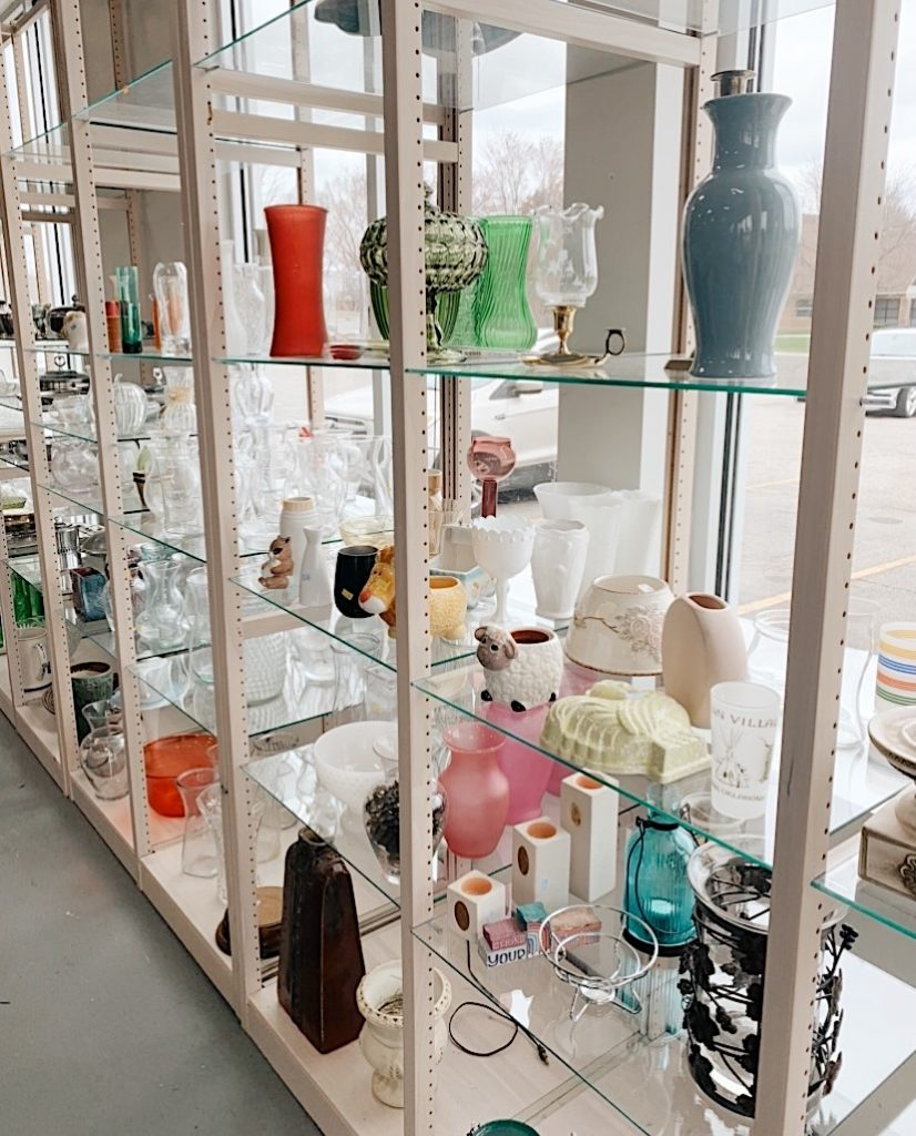 vases and glassware on a clear glass shelf